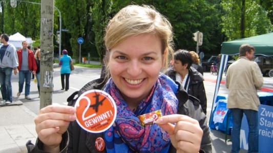 Katharina Schulze wirbt mit Flyern, Aufklebern und Nimm-Zwei-Bonbons für zwei statt drei Startbahnen am Münchner Flughafen.
